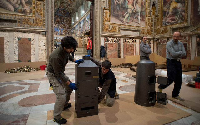 Workers prepare the stoves that will be used to burn the ballots during the next conclave in the Sistine Chapel at the Vatican in this photo released by Osservatore Romano March 7, 2013. (Photo by Osservatore Romano/Reuters)