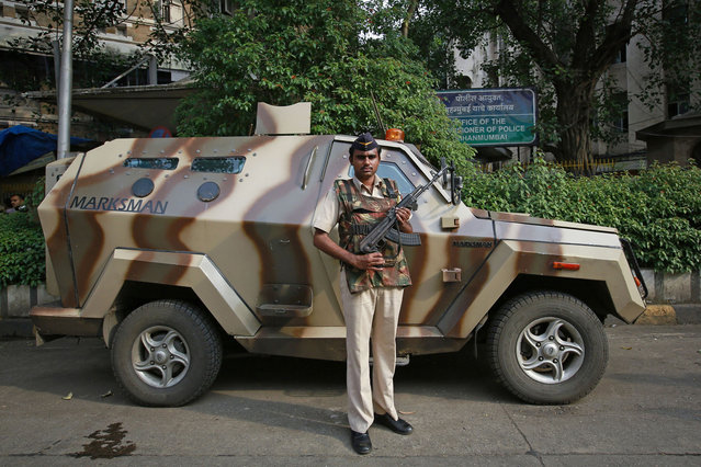 A Mumbai police constable poses as he stands guard next to an armored vehicle outside the police commissioner's office in Mumbai on October 1, 2014. In India, the Rapid Action Force (RAF) are called on for violent disorder that the police are unable to contain. They require an on-the-spot magistrate's consent and must issue a warning before each escalation of the use of force, from verbal warning to water cannon and tear gas, then to rubber bullets or baton rounds, and then to firearms. (Photo by Danish Siddiqui/Reuters)