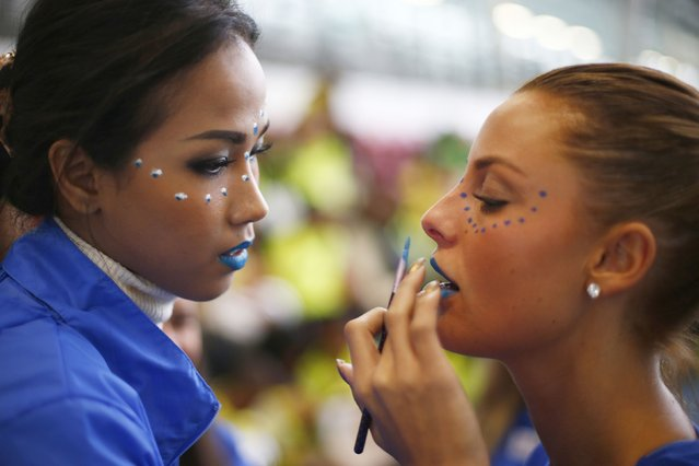 Miss Thailand Maya Nonthawan Thongleng applies face paint to Miss Norway Monica Olivia Pedersen during the Miss World sports competition at the Lee Valley sports complex in north London, November 26, 2014. Contestants from 126 countries are in London to compete in the 2014 Miss World competition. (Photo by Andrew Winning/Reuters)