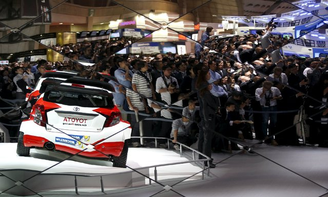 Visitors and members of the media are reflected on a wall at Toyota Motor Corp's booth during a presentation at the 44th Tokyo Motor Show in Tokyo, Japan, October 28, 2015. (Photo by Toru Hanai/Reuters)