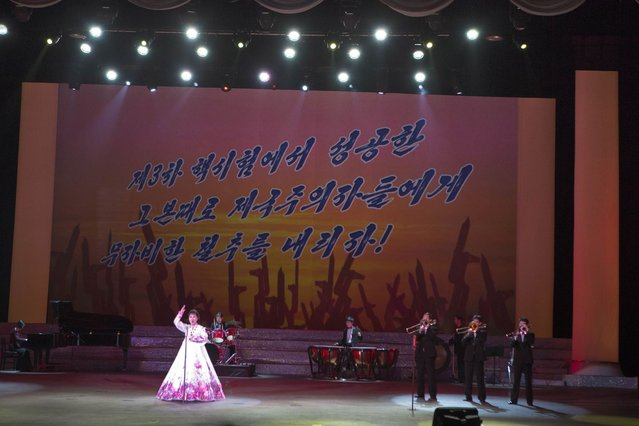 """A North Korean musical performance is held in Pyongyang with the words """"Let's strike the imperialists mercilessly with the same success we had carrying out the 3rd nuclear test"""" projected on a screen, on Sunday, February 17, 2013. (Photo by David Guttenfelder/AP Photo)"""
