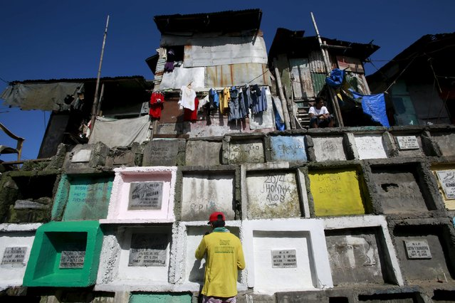 """A man repaints the tomb of his departed relative buried in an """"apartment-style"""" grave inside a cemetery in Navotas city, north of Manila October 31, 2015. (Photo by Romeo Ranoco/Reuters)"""