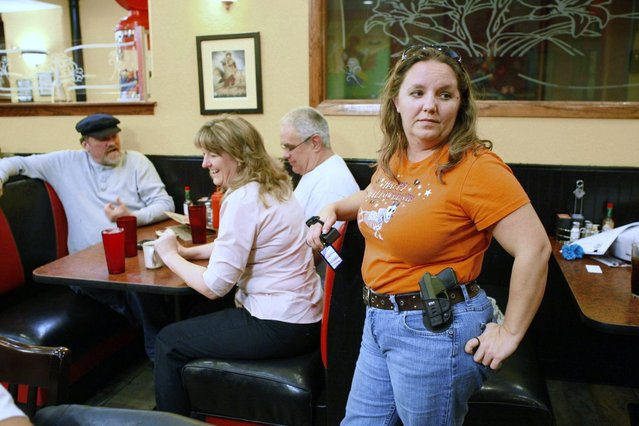 Morgan Meritt of Del City, Oklahoma, joins other members of the Oklahoma Open Carry Association (OKOCA) wearing unconcealed side arms as they gather at Beverly's Pancake House in Oklahoma City November 1, 2012. A new Oklahoma law took effect November 1 allowing anyone with a concealed weapon license to carry their firearms openly in a holster or belt. (Photo by Bill Waugh/Reuters)