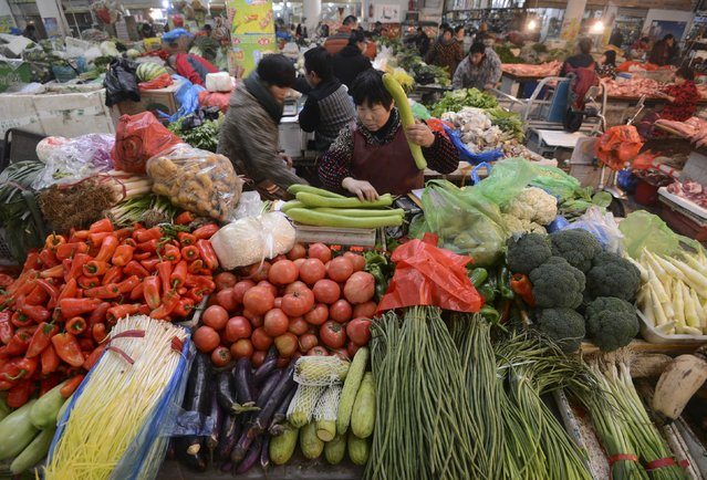 A vendor (C) weighs vegetable at a market in Fuyang, Anhui province December 10, 2014. China's annual consumer inflation eased to a five-year low of 1.4 percent in November, signalling persistent weakness in the world's second-largest economy and giving policymakers more room to ease policy to support growth. (Photo by Reuters/Stringer)