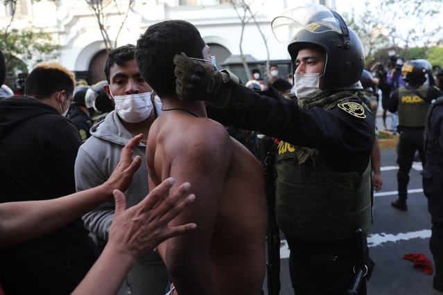 A police officer places a protective face mask on a protester who was detained near Congress where lawmakers swore-in a new president after voting to oust President Martin Vizcarra the day before, in Lima, Peru, Tuesday, November 10, 2020. Peru swore in businessman and head of Congress Manuel Merino Tuesday who is unknown to most and was recently accused of trying to secure the military's support for a congressional effort to boot the nation's last leader out over unproven corruption allegations. (Photo by Rodrigo Abd/AP Photo)