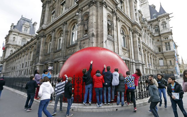 Children play with a huge red ball which is installed outside the Hotel de Ville City Hall as part of the RedBall Project by artist Kurt Perschke in Paris April 19, 2013. The RedBall Project is touring Paris from April 18 to 28, 2013, changing its location each day. (Photo by Charles Platiau/Reuters)