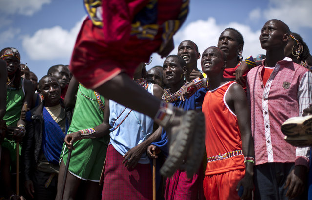 Maasai warriors look up as a competitor makes the high jump, in which athletes must touch a high line with the top of their heads, at the annual Maasai Olympics in the Sidai Oleng Wildlife Sanctuary near to Mt. Kilimanjaro, southern Kenya, Saturday, December 13, 2014. (Photo by Ben Curtis/AP Photo)