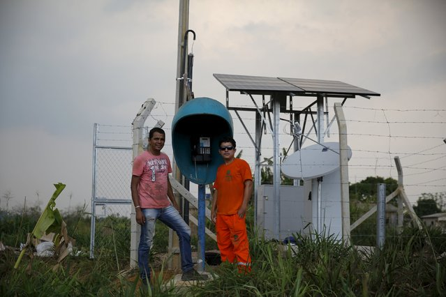 Telecom workers Marcos (R) and Caio (L), pose next to a phone booth that they built in Rio Pardo next to Bom Futuro National Forest, Porto Velho, Rondonia State, Brazil, August 31, 2015. (Photo by Nacho Doce/Reuters)