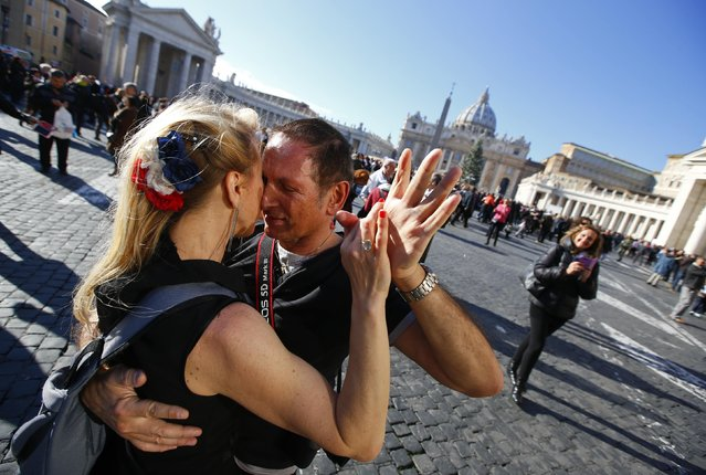 "A couple dances a tango in front of Saint Peter's basilica at the Vatican, December 17, 2014. At the rear edge of the square more than 2,000 people, who came to Rome from all over Italy for the 78th birthday of Pope Francis, danced in ""A tango for Pope Francis"" event as music blared. (Photo by Tony Gentile/Reuters)"