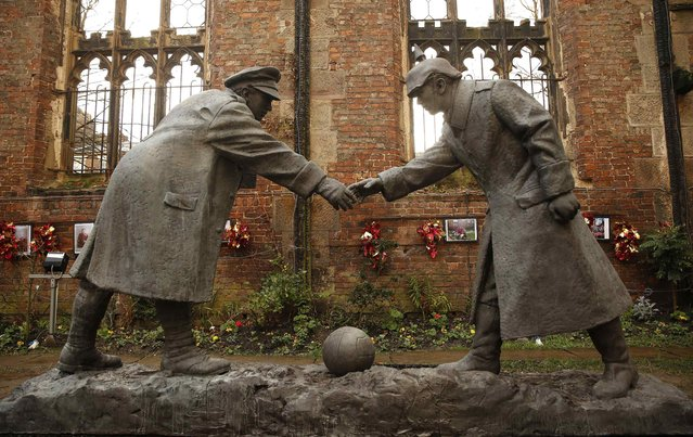 """A resin sculpture, called """"All Together Now"""", by artist Andrew Edward's is seen after being unveiled in the remains of St Luke's Church in Liverpool, northern England December 15 , 2014. The sculpture, depicting the Christmas Day football match between German and British soldiers fighting on the front line in World War One in 1914, will be displayed in the church that was damaged during German bombing of Liverpool in 1941. (Photo by Phil Noble/Reuters)"""