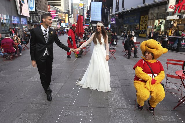 Berta and Jose Fernandez from Spain walk though Times Square as they pose for wedding photos in the Manhattan borough of New York November 11, 2015. (Photo by Carlo Allegri/Reuters)