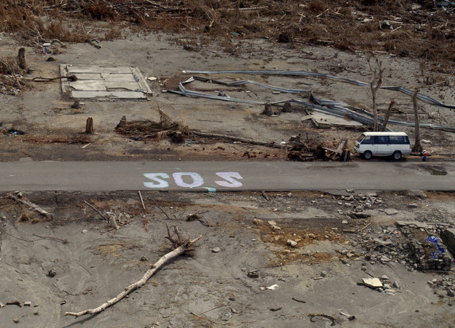 In this January 8, 2005 file photo, a huge SOS sign remains on a road leading to Meulaboh, southeast of Banda Aceh, the capital of Aceh province, during a continuing sortie by US Navy Sea Hawk helicopters from the US aircraft carrier USS Abraham Lincoln in northwest Indonesia. (Photo by Achmad Ibrahim/AP Photo)
