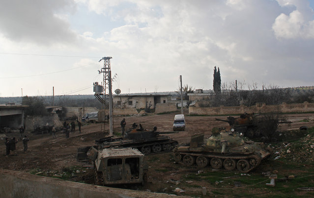 Rebel fighters stand near tanks inside al-Hamidiyeh base, one of two military posts they took control of from forces loyal to Syria's President Bashar al-Assad in the northwestern province of Idlib, December 15, 2014. (Photo by Reuters/Stringer)