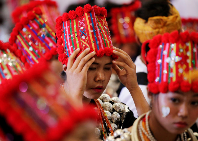 A woman adjusts her headwear as she waits for Pope Francis to arrive to lead a Mass at St Mary's Cathedral in Yangon, Myanmar November 30, 2017. (Photo by Max Rossi/Reuters)