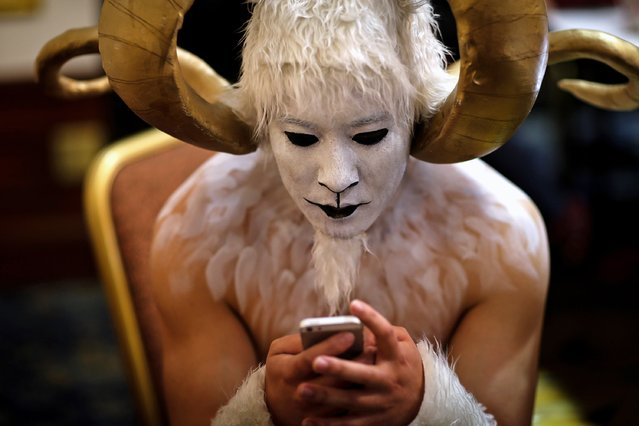 A performer in a ram costume looks at his phone backstage during a performance in Kunming, Yunnan province December 30, 2014. (Photo by Wong Campion/Reuters)