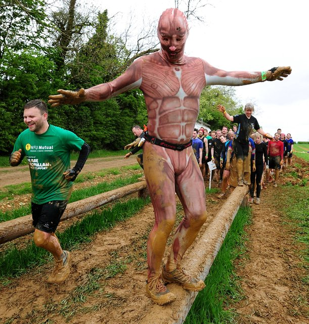 Competitors taking part in the Race Race Dirty weekend at Burghley House, Stamford, May 11, 2013. Rat Race consists of 200 obstacles over 20 differently-themed zones over a distance of 20 miles. (Photo by Rui Vieira/PA Wire)