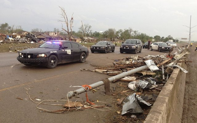 Law enforcement officials arrive on the scene after a huge tornado struck Moore, Oklahoma, near Oklahoma City, May 20, 2013. (Photo by Richard Rowe/Reuters)