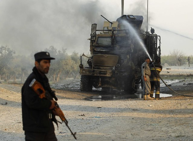 Afghan firefighters spray water on a U.S. armoured vehicle after a suicide attack on the outskirts of Jalalabad, January 5, 2015. A suicide attacker targeted a U.S. convoy on the outskirts of Jalalabad on Monday but so far no causalities have been reported yet, provincial spokesman Ahmadzia Abdulzai said. (Photo by Reuters/Parwiz)