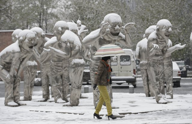 A woman holding an umbrella walks past the sculpture by Chinese artist Yue Minjun beside a road during a snow in Beijing, China, November 22, 2015. (Photo by Jason Lee/Reuters)