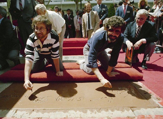 Moviemakers Steven Spielberg, left, and George Lucas , the two men responsible for the six most popular films of all time sign their names in cement Wednesday, May 16, 1984 during festivities at Mann 's Chiness theatre in Hollywood. (Photo by Wally Fong/AP Photo)