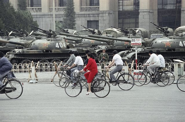 A wall of tanks and APCs greet bicycle commuters near Tiananmen Square, on June 13, 1989, in Beijing. (Photo by Sadayuki Mikami/AP Photo)