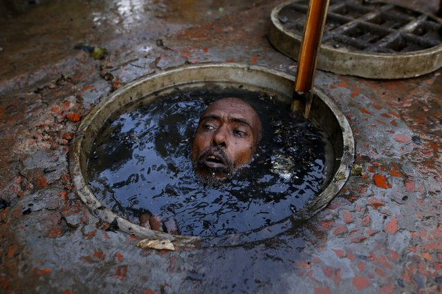 A man prepares to dive down into a blocked sewer in the Bangladeshi capital Dhaka on May 23, 2018. The people who do the work aren't even given any protective clothing or goggles and have to dig out the clogged-up muck with a stick or their bare hands. More than 14 million people live in the capital which has been hit by floods caused by heavy rains and an inadequate drainage system. The people who do the thankless task get paid between $6-10 a day by the Dhaka City Corporation. Despite not being given any protective gear the workers are expected to dive down into the sludge, usually topless, to unblock the city's underground pipes. The men are usually given a long stick to help them. You might think your job's bad but these sewer cleaners have to plunge into stinking filth with no protective gear. (Photo by Rehman Asad/Barcroft Media)