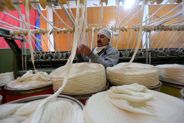 A Kashmir laborer works inside a silk factory on the outskirts of Srinagar, the summer capital of Indian Kashmir, 01 December 2015. Indian Kashmir, once famous for silk industry employing thousands of people, is now facing challenges due to competition with other countries. Chinon, Chiffon and Charmous were some silk varieties made in Kashmir. (Photo by Farooq Khan/EPA)
