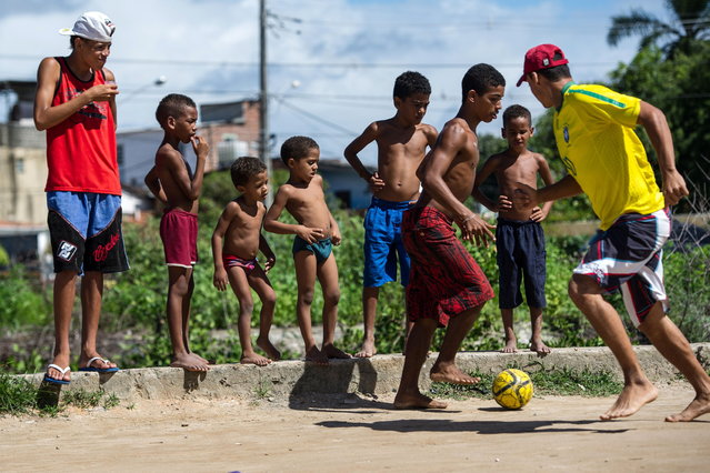 Boys play football in a shantytown of Olinda, about 18 km from Recife in northeastern Brazil, on June 18, 2013 as the FIFA Confederations Cup Brazil 2013 football tournament is being held in the country. The historic centre of Olinda is listed as an UNESCO World Heritage Site. (Photo by Yasuyoshi Chiba/AFP Photo)