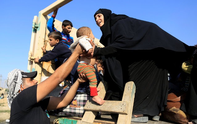 A soldier hands a baby to the mother, who had just fled the Samah district of eastern Mosul, on board a military truck at the Iraqi Special Forces checkpoint in Kokjali, east of Mosul, Iraq November 5, 2016. (Photo by Zohra Bensemra/Reuters)