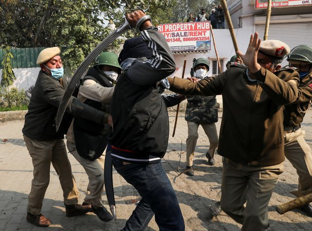 A man wields his sword against a policeman during a clash between protesting farmers and a group of people shouting anti-farmer slogans, at a site of the protest against farm laws at Singhu border near New Delhi, India on January 29, 2021. (Photo by Anushree Fadnavis/Reuters)