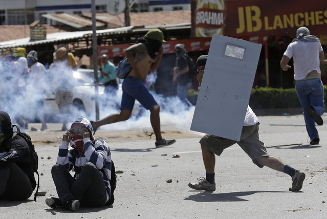 A protester runs with a make-shift shield, right, as others throw rocks at police who are firing tear gas at them a few miles from the soccer stadium where Spain and Italy will play in a Confederations Cup semifinal soccer game in Fortaleza, Brazil, Thursday, June 27, 2013.  It's the latest in a series of massive, nationwide protests that have hit Brazil since June 17. Demonstrators are angered about corruption and poor public services despite a heavy tax burden. Protests are also denouncing the billions of dollars spent to host the World Cup and the 2016 Olympics in Rio - money they say should be going toward better hospitals, schools, transportation projects and schools. (Photo by Natacha Pisarenko/AP Photo)
