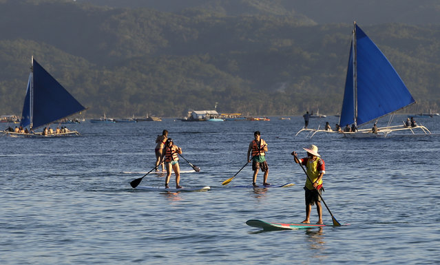 "Tourists learn to paddle in the sea by the country's most famous beach resort island of Boracay, in central Aklan province, Philippines, Tuesday, April 24, 2018. Thousands of workers will be affected when the island closes after Philippine President Rodrigo Duterte ordered its closure on April 26 for up to six months after saying the waters off its famed white-sand beaches had become a ""cesspool"" due to overcrowding and development. (Photo by Aaron Favila/AP Photo)"