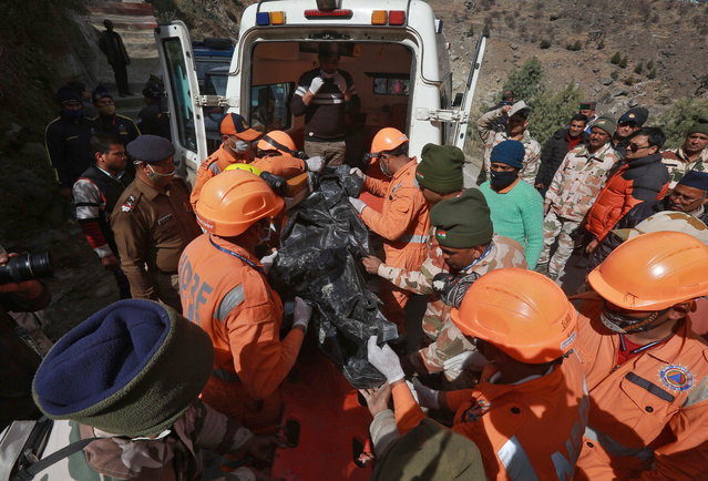 Members of National Disaster Response Force (NDRF) remove the body of a victim after recovering it from the debris during a rescue operation outside a tunnel after a part of a glacier broke away, in Tapovan in the northern state of Uttarakhand, India, February 9, 2021. (Photo by Reuters/Stringer)