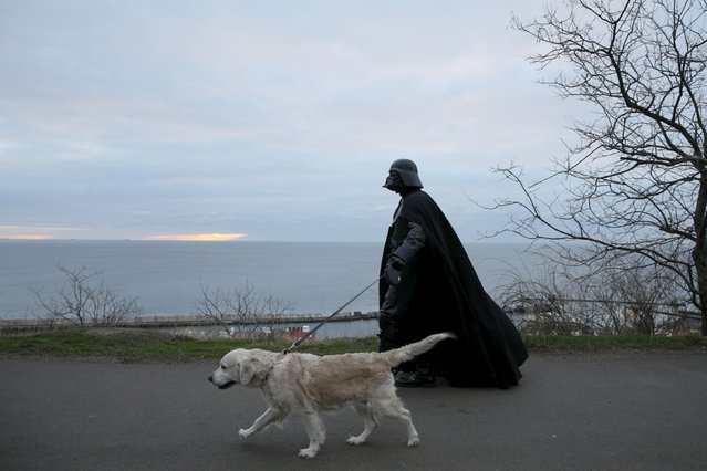 Darth Mykolaiovych Vader, who is dressed as the Star Wars character Darth Vader, poses for a picture as he walks his dog in a park in Odessa, Ukraine, December 3, 2015. (Photo by Valentyn Ogirenko/Reuters)