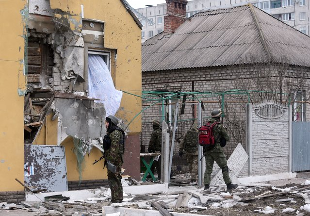 Ukrainian servicemen patrol around a damaged building  after shelling  in the southern Ukrainian port city of Mariupol on 24, 2015. (Photo by AFP Photo/Stringer)
