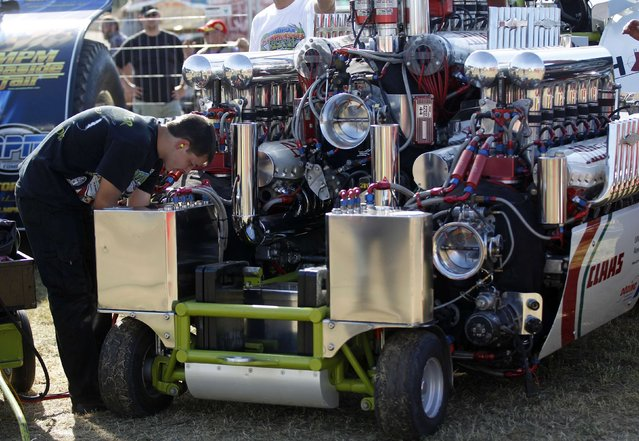 A mechanic checks a tractor motor during the Tractor Pulling Euro Championships in the western German town of Fuechtorf September 9, 2012. Eighty teams from across Europe participated in the two-day competition where high-powered tractor prototypes must pull a trailer down a 100-metre (328 ft) track as far as possible. (Photo by Ina Fassbender/Reuters)
