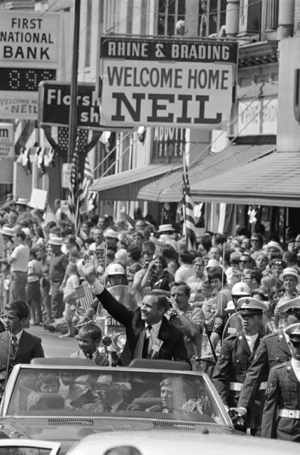 Neil Armstrong, the first man to walk on the moon and a hero to the world, waves to the hometown folks on September 6, 1969 during a big homecoming parade in his honor at Wapakoneta, Ohio. Armstrong's son, Mark, is beside him. (Photo by AP Photo)