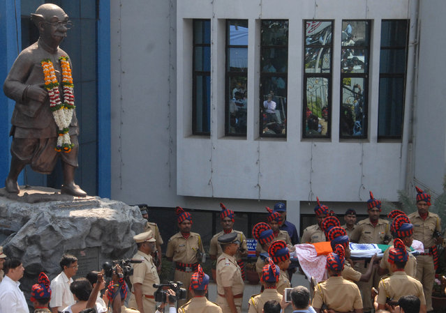 "Security officers carry the body of acclaimed Indian cartoonist R. K. Laxman past a statue of the ""Common Man"", in Pune, India, Tuesday, January 27, 2015. Laxman, who created the innocuous character the ""Common Man"" who held up a mirror to the absurdity and silliness of Indian politicians, died of multiple-organ failure Monday, his doctor said. (Photo by Nitin Lawate/AP Photo)"
