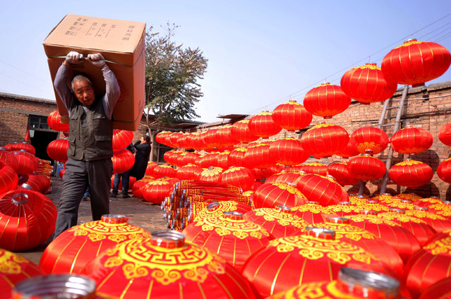 This photo taken on November 10, 2016 shows a man carrying a box of lanterns at a lantern workshop in a village in Shijiazhuang, north China's Hebei province. China's courier services are planning ahead to cope with Singles' Day, an annual e-commerce shopping spree in China that falls on November 11, state media reported. (Photo by AFP Photo/Stringer)
