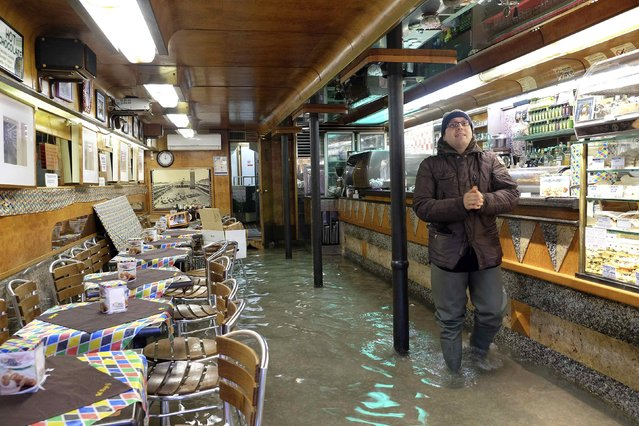A man stands inside a bar during a period of seasonal high water in Venice, February 6, 2015. (Photo by Manuel Silvestri/Reuters)