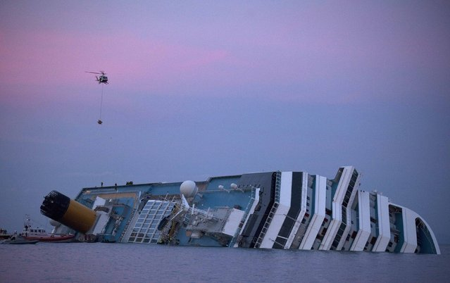 A helicopter approaches the Costa Concordia cruise ship that ran aground off the west coast of Italy at Giglio island at dusk in this January 19, 2012 file photo. (Photo by Paul Hanna/Reuters)