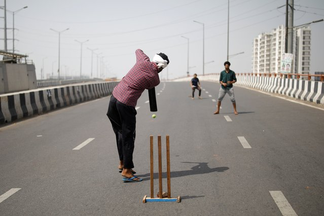 Farmers play cricket on a deserted highway road during a 12-hour strike, as part of protests against farm laws, at the Delhi-Uttar Pradesh border in Ghaziabad, India, March 26, 2021. (Photo by Adnan Abidi/Reuters)
