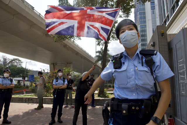 A pro-democracy supporter waves a British flag as police officers stand guard outside a court in Hong Kong Thursday, April 1, 2021. Seven pro-democracy advocates, including media tycoon Jimmy Lai and veteran of the city's democracy movement Martin Lee, are expected to be handed a verdict for organizing and participating in an illegal assembly during massive anti-government protests in 2019 as Hong Kong continues its crackdown on dissent. (Photo by Vincent Yu/AP Photo)