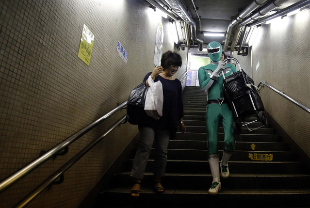 """Tadahiro Kanemasu a.k.a the """"Carry-Your-Pram-Ranger"""" carries a woman's shopping cart at the station in Tokyo August 23, 2013. In a green outfit with silver trim and matching mask, a superhero waits by the stairs of a Tokyo subway station, lending his strength to the elderly, passengers lugging heavy packages and mothers with baby strollers. (Photo by Yuya Shino/Reuters)"""