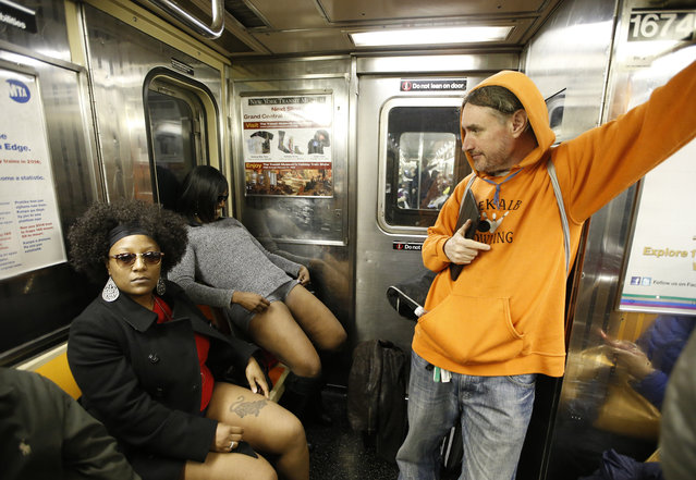 A subway rider glances behind him as two women disrobe to their underwear during the 15th annual No Pants Subway Ride Sunday, January 10, 2016, in New York. (Photo by Kathy Willens/AP Photo)