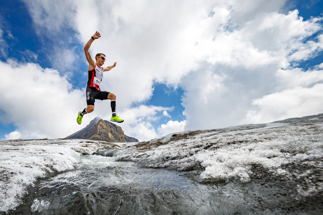 "A participant jumps above a water stream on the Tsanfleuron glacier approaching the finish line of the Glacier 3000 run above the alpine resort of Les Diablerets, Switzerland, Saturday, August 4, 2018. The 26 kilometer-long course starts at 1050 meters above sea level in the village of Gstaad reaching a final altitude of 2950 meters on the ""Glacier 3000"" for a total elevation gain of 2015 meters along the course. (Photo by Valentin Flauraud/KEYSTONE)"