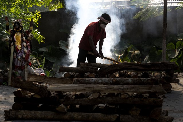 A man makes a cremation platform to burn a body of a person who died of COVID-19 in Gauhati, India, Tuesday, April 27, 2021. (Photo by Anupam Nath/AP Photo)