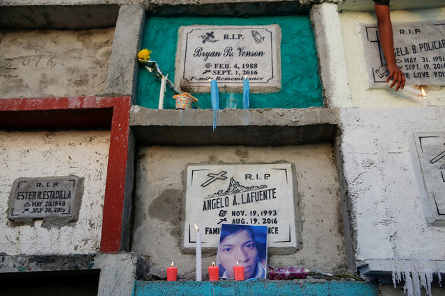 A photograph of Angelo Lafuente, whose body, riddled with bullets, was found by a filthy river that feeds into the Manila bay, is placed with candles on his grave on the All Saints Day in Manila, Philippines November1, 2016. (Photo by Damir Sagolj/Reuters)