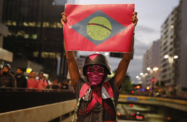 A demonstrator holds a banner with the shape of the Brazilian flag during a protest against the fare hike on public transportation in in Sao Paulo, Brazil, Tuesday, January 19, 2016. The protest was organized by the Free Fare Movement, the same group that initiated mass anti-government demonstrations that filled streets across Brazil in 2013, after Sao Paulo Mayor Fernando Haddad raised bus fares from 3.50 reals to 3.80 reals. (Photo by Andre Penner/AP Photo)