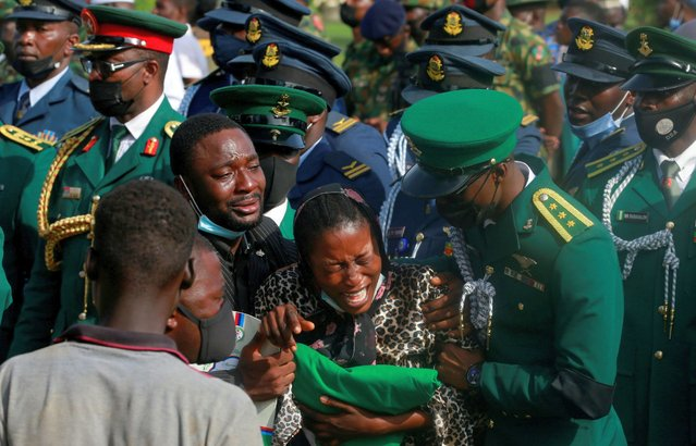 A woman reacts during the burial of victims of a military airplane crash carrying Nigeria's army chief, Lieutenant General Ibrahim Attahiru, and ten other officers, in Abuja, Nigeria on May 22, 2021. (Photo by Afolabi Sotunde/Reuters)